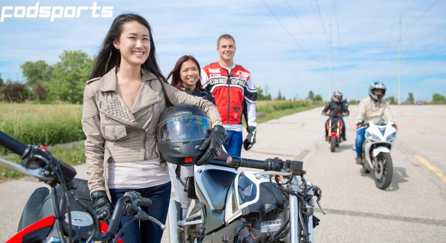Two female motorcycle riders and one male rider resting on the side of the road
