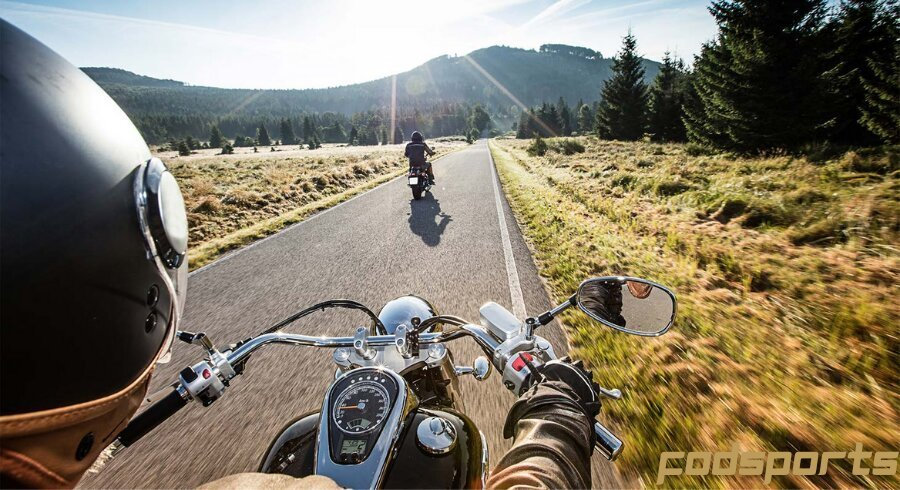 Two motorcycle riders are enjoying riding in the suburbs
